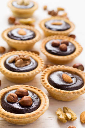 nutty: Nutty chocolate dessert small tarts on a white background. Stock Photo