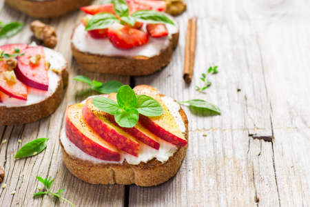 whole wheat toast: bruschetta with peaches, plums, strawberries and cottage cheese. Top view with copy space