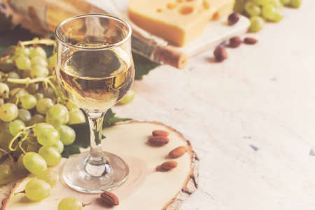 vins: White wine in the glass on the background of grape and cheese, tinted, copy space