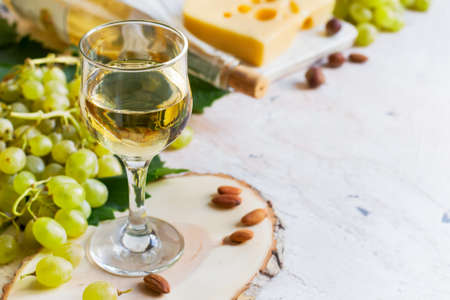 vins: White wine in a glass on a white background, copy space.