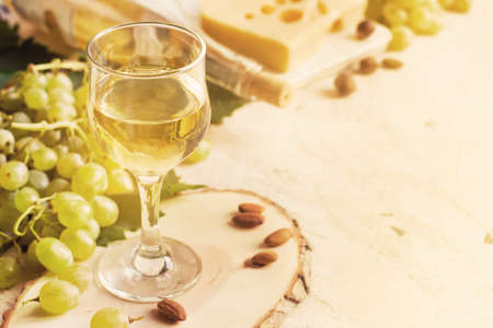 glass of white wine, cheese and grapes, tinted and copy space. Stock Photo