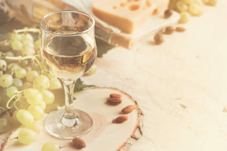 Vintage background with a glass of white wine and grapes, tinted, copy space