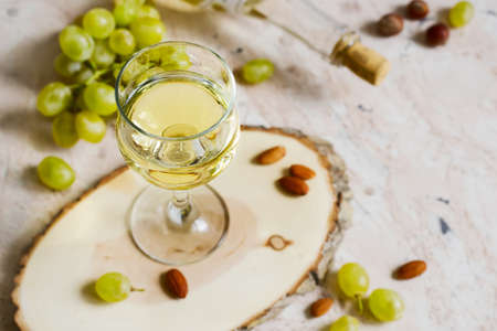 Glass of white wine and a bunch of grapes. Stock Photo