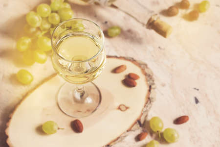 Glass of white wine on the background of grapes and nuts, tinted.