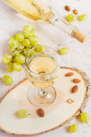 vins: White wine in a glass and a bunch of grapes, tinted.