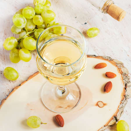 White wine in the glass and a bunch of grapes. tinted. Stock Photo