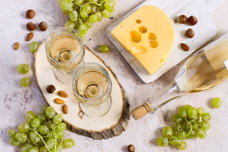 Two glasses of white wine, cheese and grapes. Top view.