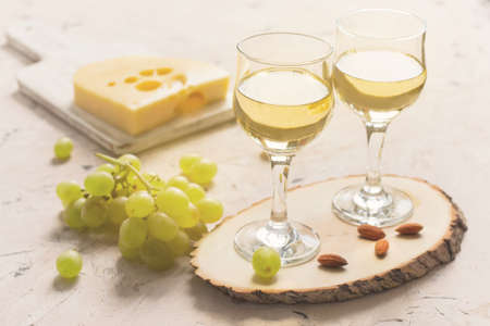 Two glasses of white wine with grapes, cheese and nuts.