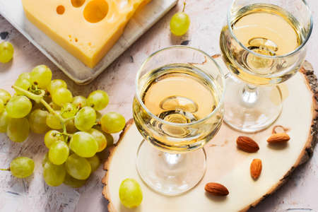 Glasses of white wine, grapes and nuts.