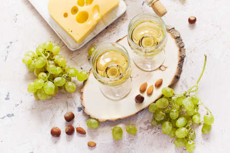 Glasses of white wine, grapes, nuts and cheese on white background