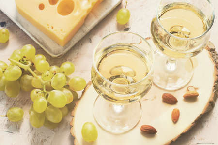 Glasses of white wine and grapes and nuts, tinted.