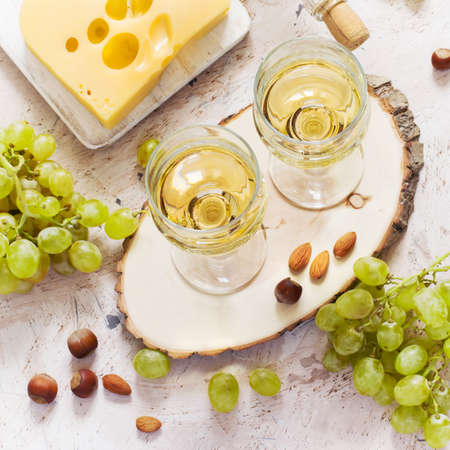 Glasses of white wine, grapes and cheese on white background.