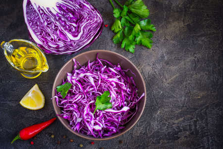 Purple cabbage salad and ingredients on a dark background. Top view with copy space