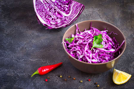 Purple cabbage salad in bowl on dark background, copy space.