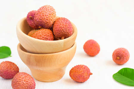 Ripe lychees in a bowl on a white background, selective focus, copy space