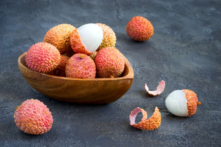 Fresh lychees in a bowl on a dark background.