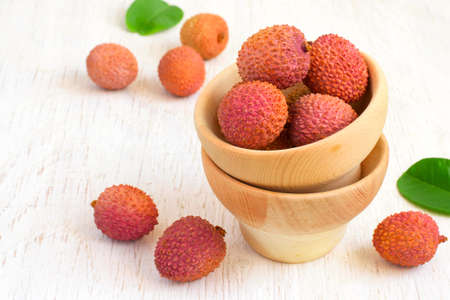 Ripe lychees in a bowl on a white background, copy space. Stock Photo