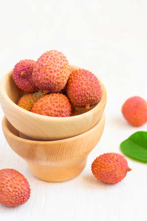 Ripe lychees in a bowl on a white background closeup, selective focus