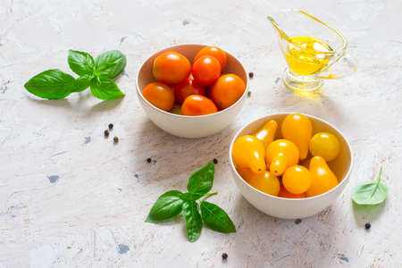 Red and yellow cherry tomatoes in a bowl with basil and olive oil.