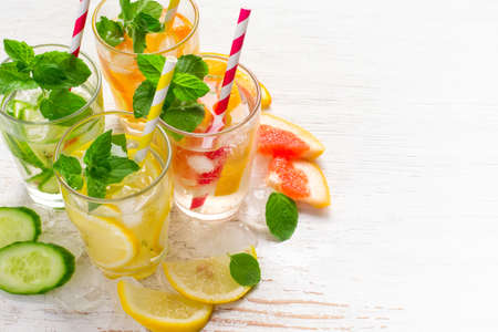 infusing: Set of Cucumber grapefruit lemon orange mint  infused water for detox on a white background. Concept of summer drinks
