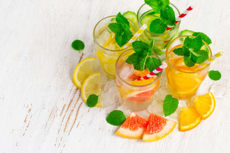 refreshment: Set of Cucumber grapefruit lemon orange mint  infused water for detox on a white background. Concept of summer drinks