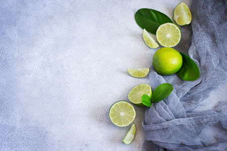 levitate: Concrete background with juicy limes. Top view with copy space.