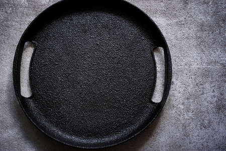 Empty rustic black cast iron plate On a concrete background. Top view with copy space