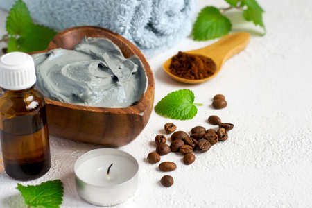 Spa setting with cosmetic blue clay mask for body, Towel  Essential oil and coffee beans Stock Photo