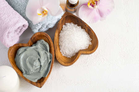 Spa background. Cosmetic face and body mask  made of blue clay, sea salt towels and orchids