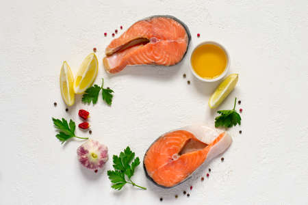 cooking oil: Fresh raw salmon steak, olive oil, lemon and spices are arranged in a circle. Top view with copy space Stock Photo