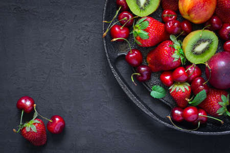 Mix of summer berries and fruits on a black plate. Top view with copy space