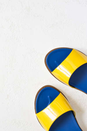 varnished: Female youth bright Yellow blue varnished summer sandals on a white background. Top view with copy space. Stock Photo