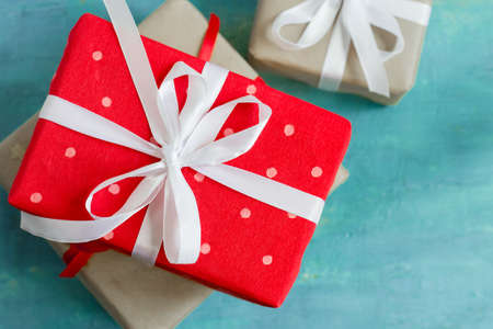enebro: Christmas boxes of gifts festively decorated On a turquoise background, selective focus.