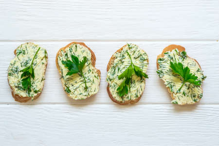 Sandwiches with herbs butter on white wooden background. Zdjęcie Seryjne