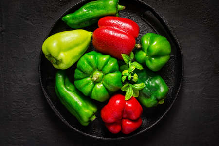 Different red and green bel peppers With drops of water On black background. Stock Photo