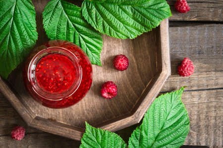 conservative: Homemade raspberry jam in a jar and fresh berries. Stock Photo