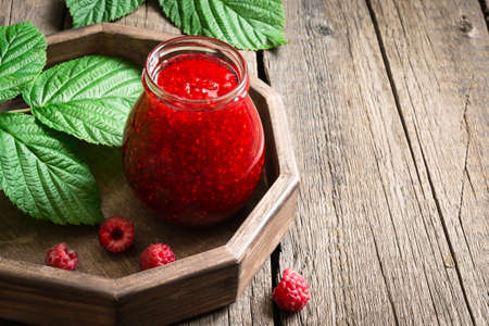 conservative: Jar with homemade raspberry jam on a tray, copy space.