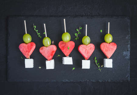Snack for Valentine's Day. Watermelon, feta and grapes on skewers. Imagens