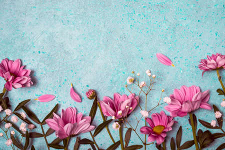 Spring Summer Creative nature background. Pink flowers border on vintage blue background