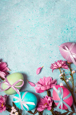 Happy Easter concept. Festive vintage background with decorated eggs and pink flowers.
