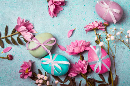 Festive vintage Easter background with decorated eggs and pink flowers.