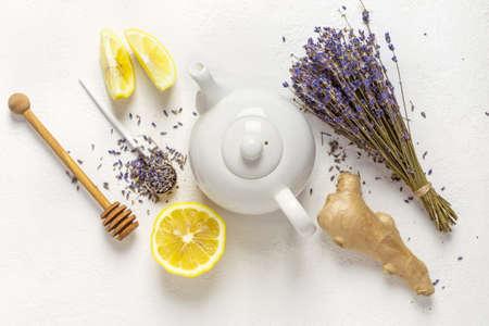 Lavender herbal tea in a white teapot, lemon and ginger.