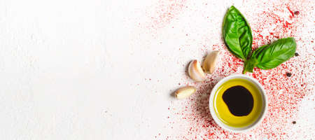 Olive oil and sprig of basil on a white background.