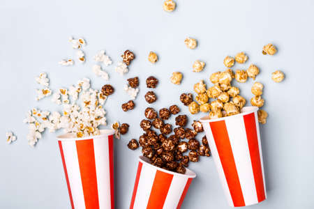 Assorted popcorn set in paper striped white red cup. Sweet and salty popcorn.