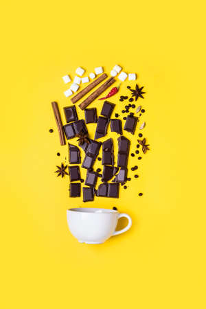 Concept hot chocolate recipe: chocolate pieces, spices and marshmallows on yellow background.