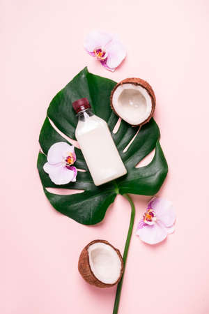 Coconut oil and tropical leaves and flowers. Hair care spa concept. Foto de archivo