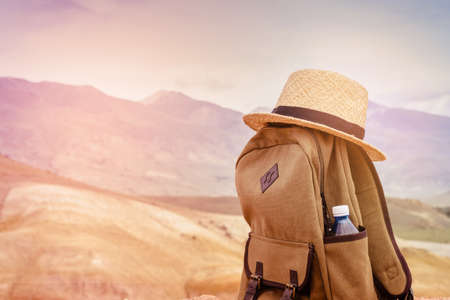 Beige backpack, bottle of water and straw hat on on top of the mountain. Active travel concept. Toning sunrise.