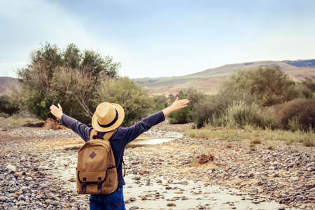 traveling boy with backpack and in straw hat looks at mountain stream.