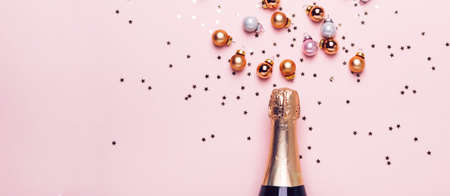 Champagne bottle and scattering of golden shiny balls and confetti on pink background, banner format. Stock fotó - 109728209
