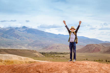 Happy boy traveler with his hands up on blue mountains background.
